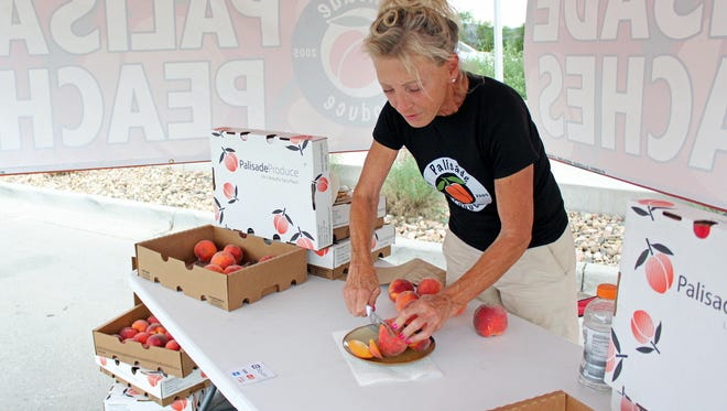 Deborah Sherman slices a Palisade peach for customers to sample at the Palisade Produce stand on North College Avenue on Wednesday.