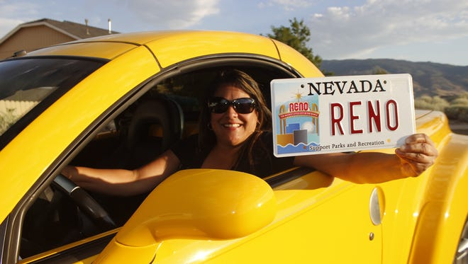 A photo of a woman holding a special Reno license plate.