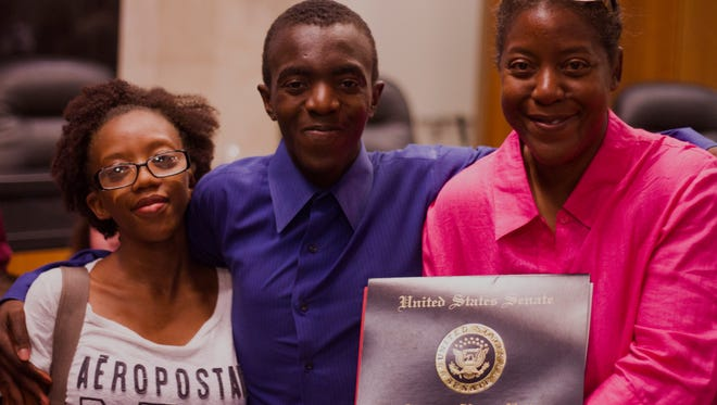 Xavier House, middle, stands with his mother and sister after graduating from the Reno Works program on Aug. 18.