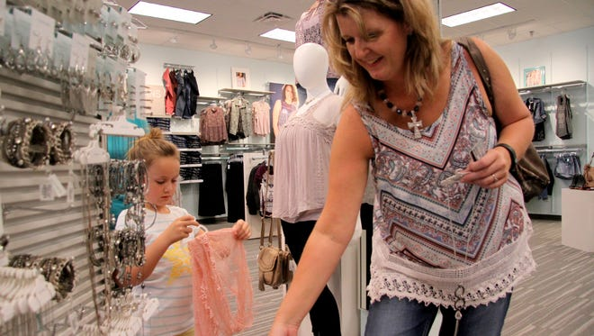 Misti Quintanilla and her niece, 7-year-old Jaislyn Rollin, shop at Maurice's on their first day in business.