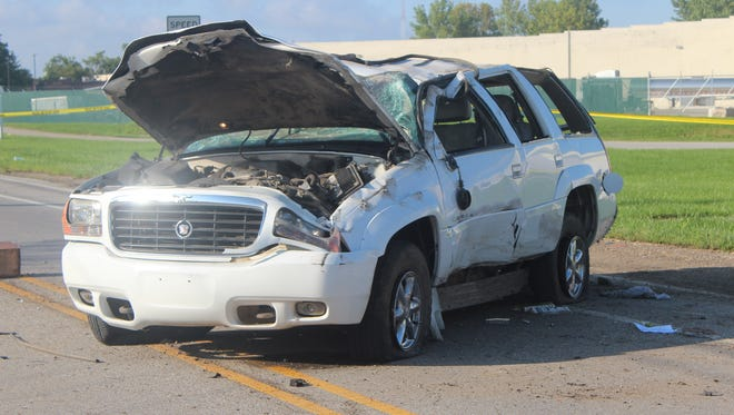 Police think the driver of this Cadillac SUV was distracted by a cell phone, causing a crash Thursday morning that killed one and critically injured two others.
