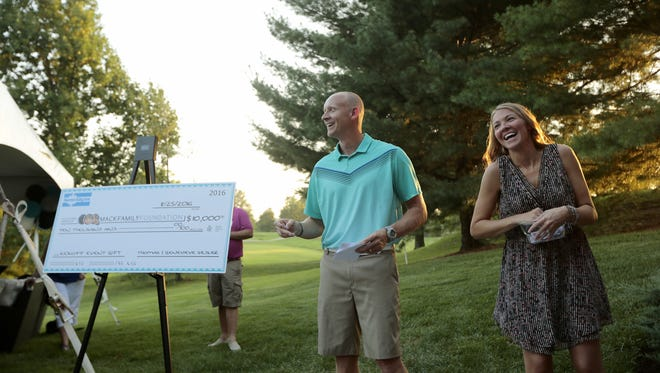 Xavier University men's basketball coach Chris Mack and his wife, Christi Mack, laugh as they pull raffle tickets following the introduction of their new Mack Family Foundation at their home in Crestview Hills, Ky.