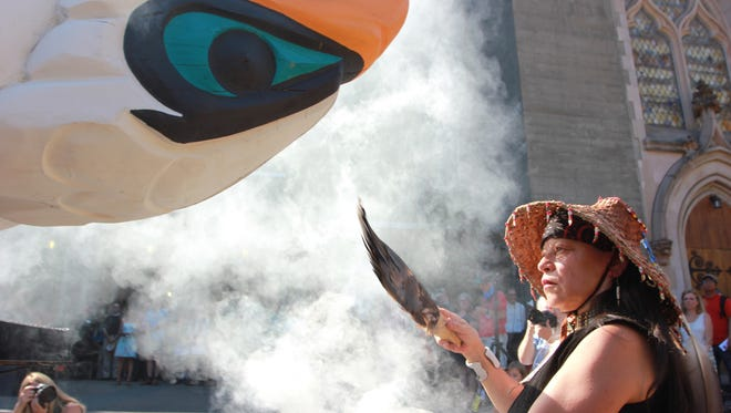 Linda Soriano of the Lummi Nation performs a smudge ceremony at Saint Mark's Episcopal Cathedral in Seattle, fanning smoke from burning sage with eagle feathers onto a totem pole, Thursday, Aug. 25, 2016.