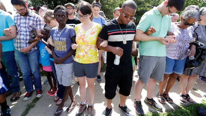 People come together for a prayer vigil after unrest in the Sherman Park neighborhood following a fatal police shooting.