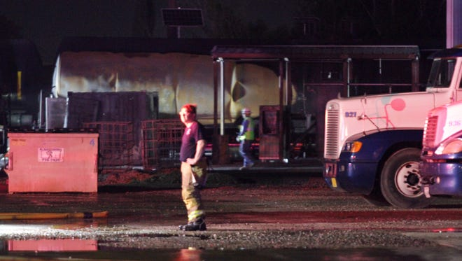 El Paso Fire Department officials inspect the scene of a fire which engulfed a rail car late Friday at a business site in the Lower Valley.