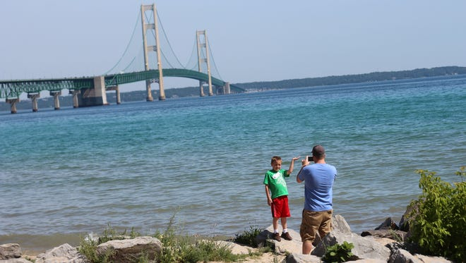 A dad and son strike a pose in front of the Mackinac Bridge in Mackinaw City, Michigan.
