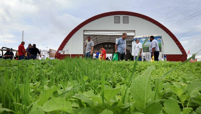 Farmers check out a cover crop demonstration at the Farm Progress Show in Boone Tuesday, Aug. 30, 2016.