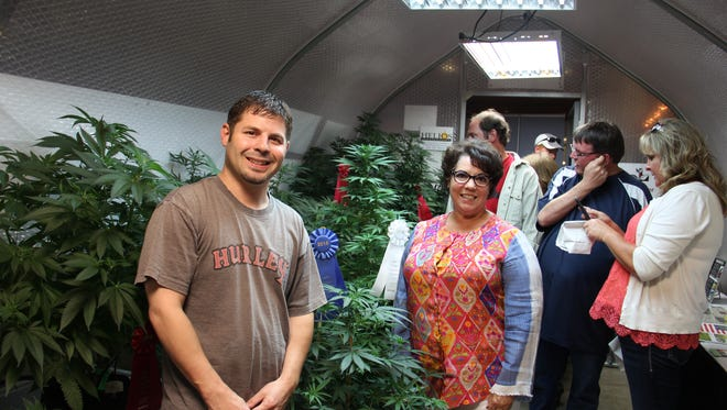 Daniel DeMeulle, left, and Carolyn Morse, right, inside the greenhouse featuring the winning cannabis plants from the Cannabis Growers Fair.
