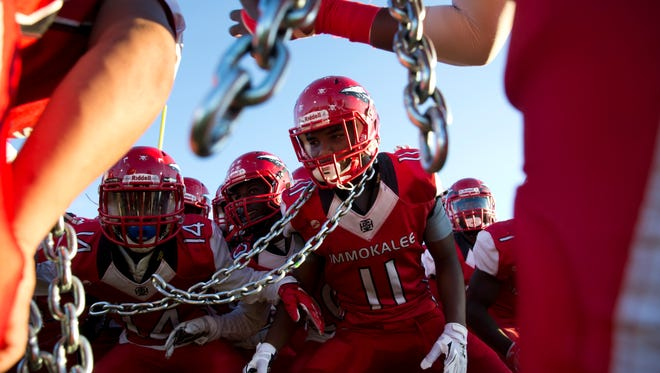 Immokalee's Jackson Malcom (11), along with the rest of the Immokalee High School team, gets pumped up as they take the field for a matchup against Barron Collier High School Friday, September 9, 2016 in Immokalee.