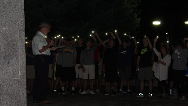 Wesley Foundation director of campus ministry Dave Glenn-Burns asks the crowd to raise their lights as friends, family and classmates gathered Monday, Sept. 12, 2016 at a vigil for UNI sophomore Nathan Twedt, who died Sept. 10 in Iowa City.
