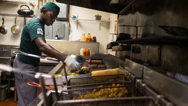 Cardell Anderson works the grill at Brooks Gourmet Burgers & Dogs in Naples, Florida on Friday, Sept. 16, 2016. National Cheeseburger Day is September 18th. Brooks made TripAdvisor's America's 10 Most Delectable Burger Joints List for two consecutive years in 2015 & 2016.