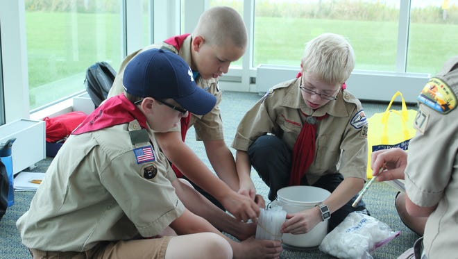 Colman Slattery, Colin Griffin and Joseph Ehmke-Zimmer from Two Rivers Troop 927 construct a mock nuclear reactor during the Boy Scout Workshop.