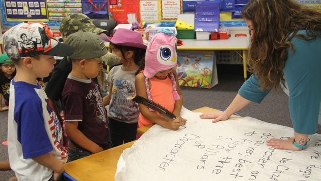Kindergartners in Chelsea Johnston's class sign their classroom Constitution.