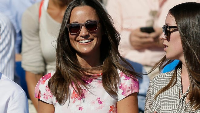 FILE- In this Friday, June 19, 2015 file photo, Pippa Middleton, left, the sister of Kate, the Duchess of Cambridge, watches the quarterfinal tennis match between Canada's Milos Raonic and France's Gilles Simon on the fifth day of the Queen's Championships in London.