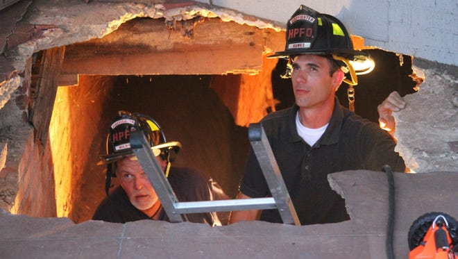 Honea Path firefighters work in a hole after a partial sidewalk collapsed Monday evening in front of Upstate Dance on north Main Street.