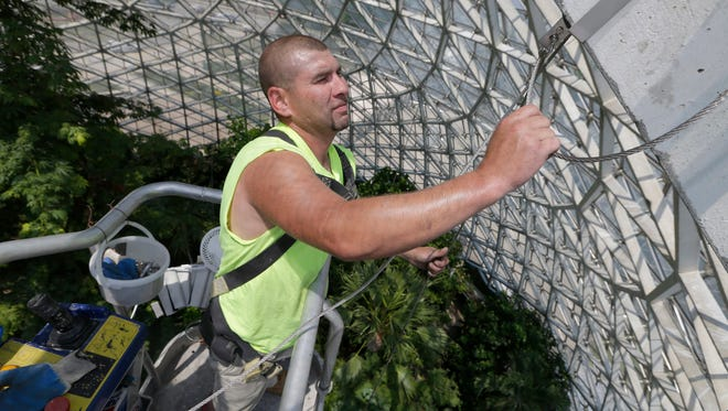 DOMES - Ken Glyzewski, a foreman with Masonry Restoration out of Milwaukee, works on placing steel cable and brackets on the on internal frame that will support wire mesh at the Tropical Dome at Mitchell Park Conservatory.  Mesh will protect public from falling concrete that could flake off frame. Monday, July 11, 2016.  -  Photo by Mike De Sisti / MDESISTI@JOURNALSENTINEL.COM
