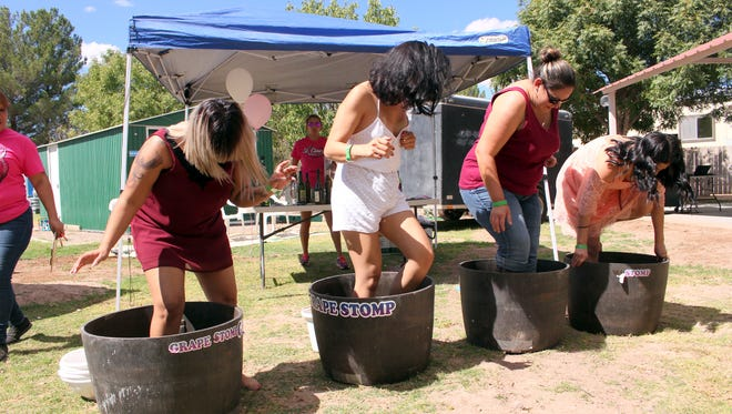 Contestants in the grape smash contest jump into barrels of grapes to see who could make the most grape juice during the St. Clair Wine Festival. The festival was hosted in support of the Cancer Support of Deming & Luna County inc. and its efforts to help its patients battle the disease.