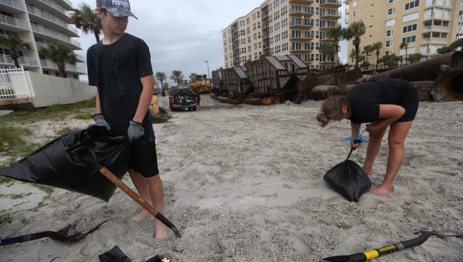 Joseph Skinner, 13, and his aunt Karla Baily of Ponte Vedra Beach fill sand bags at Jacksonville Beach on Thursday. Hurricane Matthew is expected clobber the east coast of Florida this weekend.