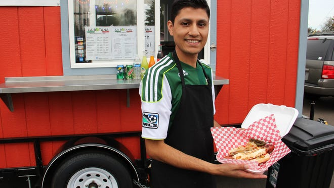 Javier Rodriguez shows off his bacon-wrapped hot dog in front of his Mexican snack cart, La Botana.