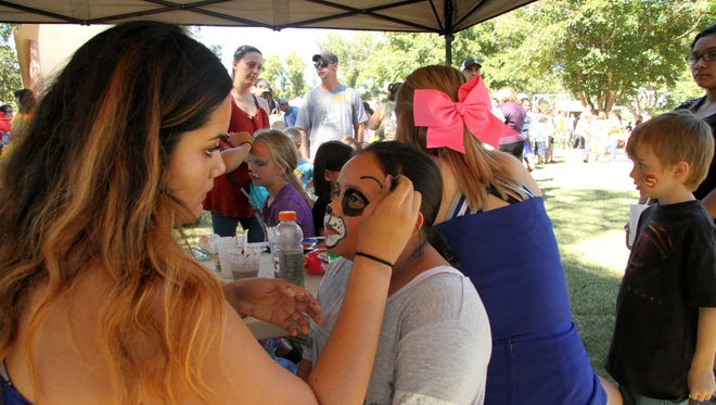 Carlsbad High School junior Rainey Trujillo paints the face of Victoria Munoz, 9, during the annual Fall-A-Palooza on Saturday.