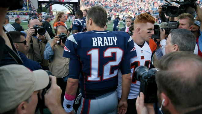 Photographers swarm as New England Patriots quarterback Tom Brady (12) and Bengals quarterback Andy Dalton (14) shake hands at midfield after the fourth quarter of the NFL Week 6 game between the New England Patriots and the Cincinnati Bengals at Gillette Stadium in Foxboro, Mass., on Sunday, Oct. 16, 2016. The Bengals fell to 2-4 with a 35-17 loss in Tom Brady's first home game since his four-game suspension.