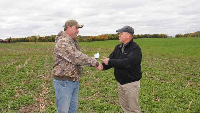 Farmer Bob Van De Loo (left) and Bill Hafs, New Water; shake on the first Fox River water quality trade in the Great Lakes basin.