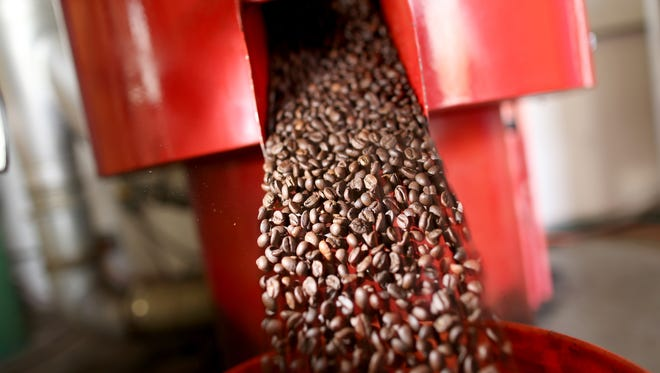 Coffee beans are seen in the roaster.