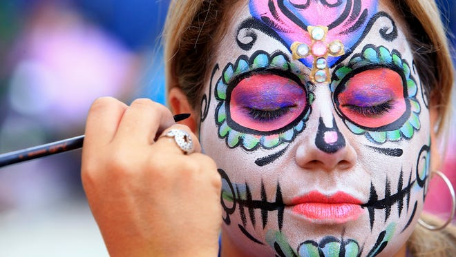 Paloma Calderon gets her face painted by Miriam Saadeh during the Dia De Los Muertos Festival on Saturday, Oct. 31, 2015, in downtown Corpus Christi. Patrons who attend Dia de los Hooks will have the opportunity to have their face painted.