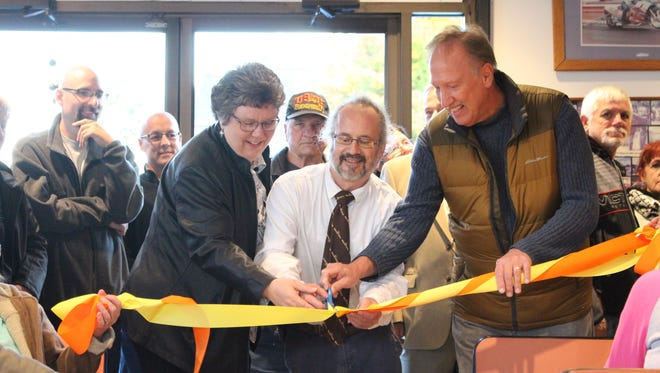 Kathy Ezawa from the Domestic Violence Shelter, Wiener King owner Jimmy Smarjeff and at-large city councilman Cliff Mears cut the orange and yellow ribbon celebrating the grand opening and 40th anniversary of Wiener King on Monday, Oct. 24, 2016. Wiener King received thousands of dollars in donations to remodel the 40-year-old restaurant.