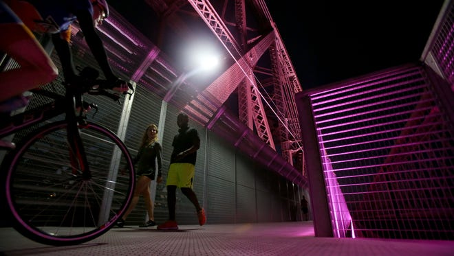 "Maritza Anderson, center, and Brandon Campbell, right, make their way across the Big River Crossing, illuminated pink for Breast Cancer Awareness Month. Lights on the newly opened Harahan Bridge boardwalk will change from ""architectural white"" to other displays for holidays and events."