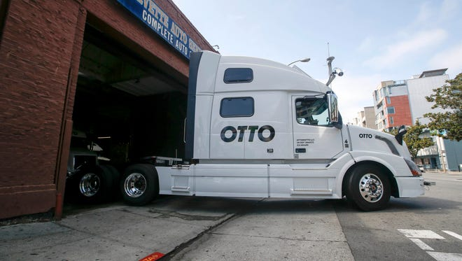 FILE - In this Aug. 18, 2016, file photo, one of Otto's self-driving, big-rig trucks leaves the garage for a test drive during a demonstration at the Otto headquarters in San Francisco. Anheuser-Busch announced on Oct. 25, 2016, that it teamed up with Otto for a 120-plus mile beer delivery that marked the world's first by a self-driving truck.
