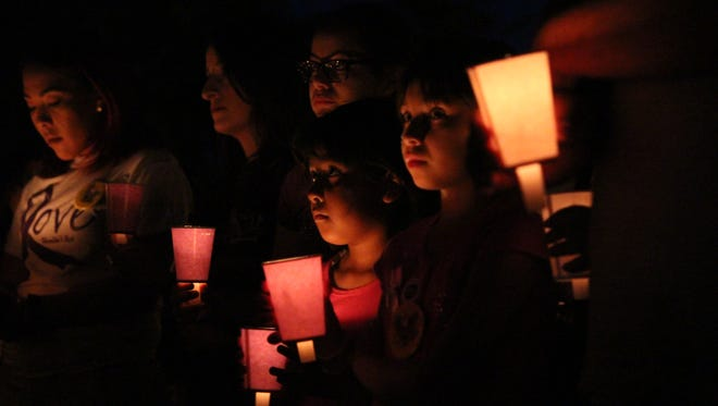 Members of Wednesday's candlelight vigil listen to prayers to help those suffering from domestic abuse or violence.