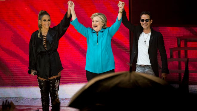 "Democratic presidential candidate Hillary Clinton stands with performers Jennifer Lopez, left, and Marc Anthony, right, during a free concert held at Bayfront Park Amphitheater in support of her ""Get Out The Vote"" campaign Saturday, Oct. 29, 2016 in Miami."