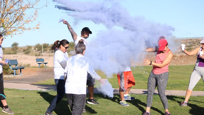 Participants in the Color Purple Fun Run on October 15. 2016 toss the last of their color dust after the run ended. The run, hosted by Luna County Friends of the Healing House, was held in effort to raise awareness for domestic violence during the month of October. Several other events throughout the month were hosted in honor of Domestic Violence Awareness Month including flamingo and ribbon placing as well as a candlelight vigil to end the month.