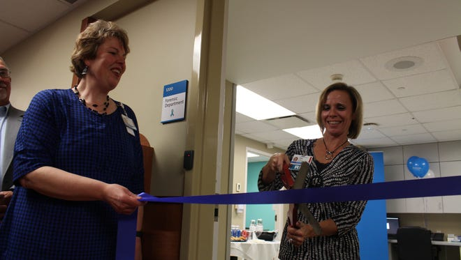 Jean Halpin, president of OhioHealth Mansfield and Shelby hospitals, holds the ribbon while Tammy Robertson, forensic nurse coordinator at the hospital, cuts the ribbon, officially opening the hospital's new Forensic Department on Tuesday. The department is a collaboration with the hospital, local law enforcement, Richland County Children Services and the Domestic Violence Shelter.