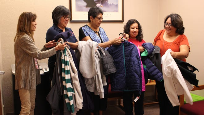 From left, Christina Eadrizz, Susanna Clemente, Yolanda Willis, Leticia Barraza and Olivia Paez sort through coats before Saturday's Stuff the Bus Fundraiser. The event is hosted by Luna County Coats for Kids in effort to ensure all students have a coat for the winter