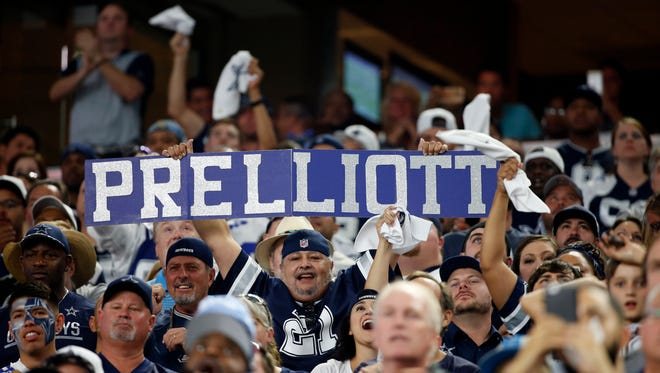Fans hold up signs that combine the name of Dallas Cowboys rookies Dak Prescott and Ezekiel Elliott as they cheer during an NFL football game against the Philadelphia Eagles on Sunday, Oct. 30, 2016, in Arlington, Texas. (AP Photo/Michael Ainsworth)