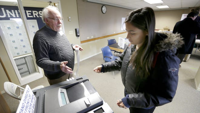 Poll worker Jim Forbeck helps Lawrence University student Loraina Stinson submit her ballot at Lawrence University's Alexander Gym in April.