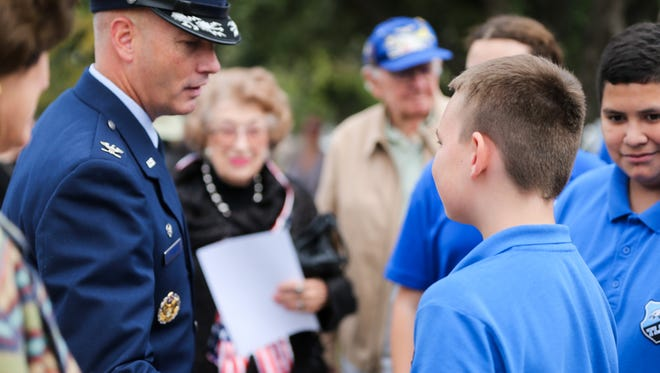 Col. Michael Downs, 17th Training Wing commander at Goodfellow Air Force Base, meets Texas Leadership Charter Academy students after a Veterans Day ceremony Friday at Fairmount Cemetery.
