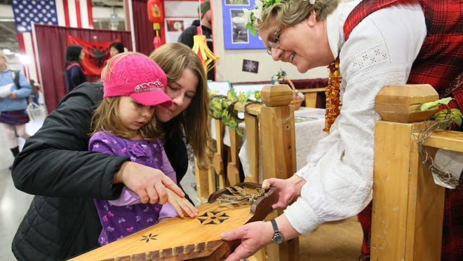 Sigrida Staks of Shorewood (right), representing the Latvian culture at the 2015 Holiday Folk Fair International, shows Isla Noller of Elkhorn and her mother, Jessica, how to play a stringed instrument called the kokle.
