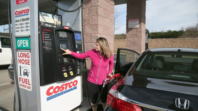 Anne Neustedter, of Brookfield, fills up her car at Costco in Pewaukee.