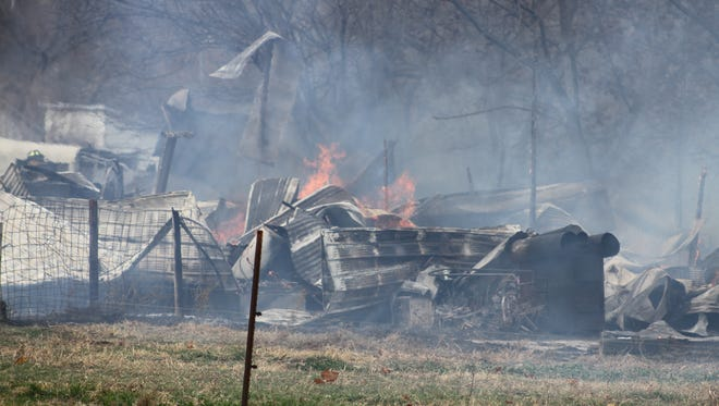 Flames poke out of rubble from a barn in rural Iowa County, about seven miles northwest of Marengo, Friday afternoon, Nov. 18.