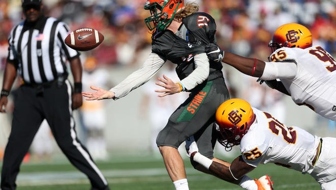 Bethune-Cookman's Arthur Williams, below, and DiShawn Ray strip FAMU quarterback Ryan Stanley during the Florida Classic in Orlando on Saturday.