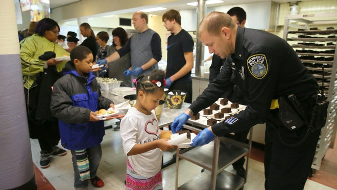 MPD officer Chris Ottaway hands a piece of cake to Olivia Eubanks, 5, as she goes through the line.