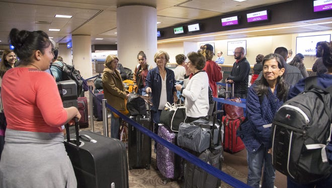 Passengers wait in line at Phoenix Sky Harbor International Airport for Thanksgiving travel on Monday, Nov. 21, 2016.
