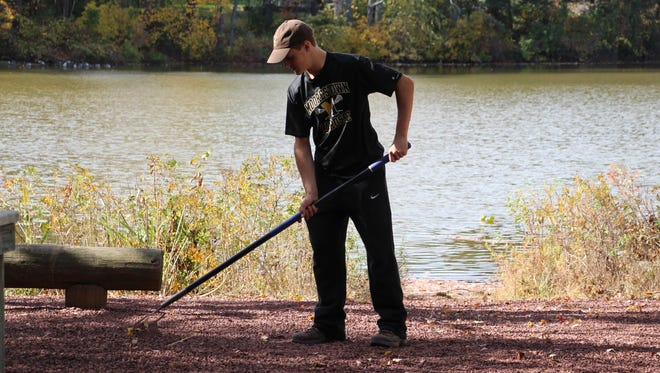 Boy Scout Alex Wright spreads gravel around  Strawbridge Lake in Moorestown and one of the log bench seats once covered by tall weeds and vines. A major clean up by scouts and other friends from the high school is his Eagle Scout project