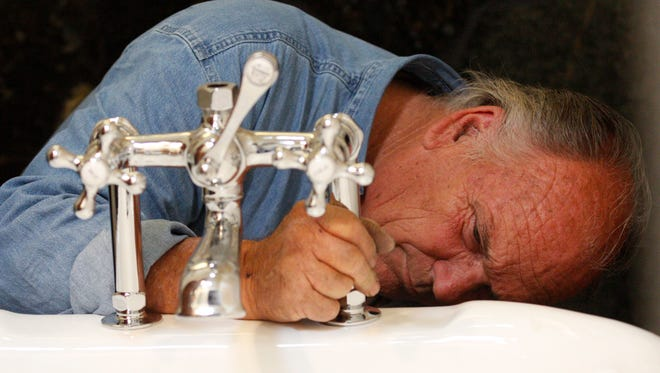 Plumber Phil Hall installs a tub that will tie into a graywater system at the Browne residence in Camarillo.