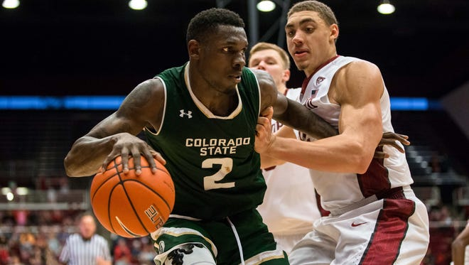 CSU's Emmanuel Omogbo tries to protect the ball from Stanford defender Reid Travis during Sunday's game at Maples Pavilion in Stanford, Calif.. The Cardinal beat the Rams 56-49.
