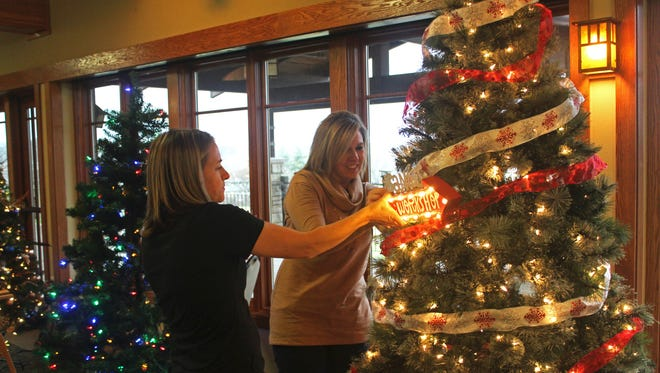 From left to right: Katy Grimes and Sonja Hawbaker, co-owners of SK Cabinetry and Design, decorate their tree on Nov. 22, 2016, in preparation for the Coralville Center for the Performing Art's Festival of Trees.