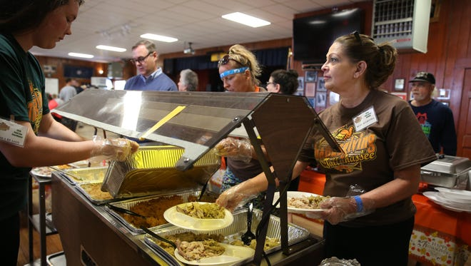 "Volunteer Beth McGrotha fixes plates of food at a Thanksgiving celebration at  American Legion Hall Post 13 on Thursday. McGrotha, a first time volunteer, said, ""This is the way to spend thanksgiving."""